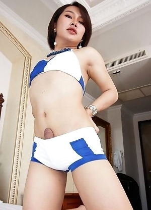 Ladyboy Touk is wearing a tight blue and white two-piece comprised of booty shorts and a little top. She sits on a chair with legs spread and begins s
