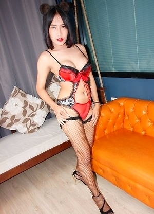 Ladyboy Meme is wearing red lingerie, black stockings, and heels. She gets up from reclining on the couch to do a little dance for the POV. After this
