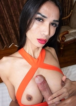 Slim Ladyboy Bella is wearing a short orange dress with big tits popping out. She sits on the chair, lowers her dress, and squeezes her tits together.