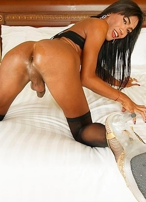 Nutty is waiting on the couch for a cock to play with. Her tight, athletic body glistens with oil underneath her skimpy black body stocking. She bends
