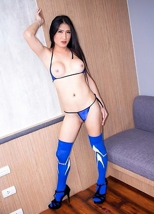 Ladyboy Tong is standing in a blue bikini with her hard cock poking out and barely covered at all.