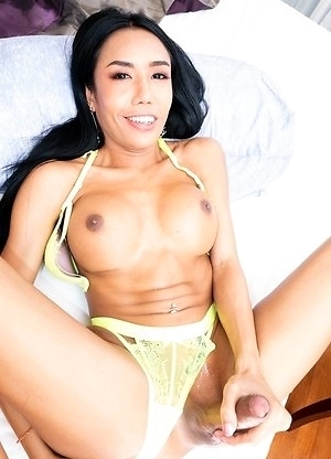 Ladyboy Mos is wearing a yellow bra and panty set that contrasts well against her tanned body.