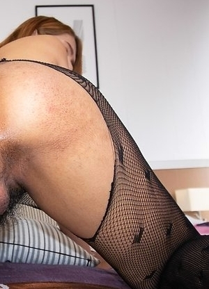 Ladyboy Bipor is by the bedside wearing a black tube top,jean booty shorts, and pantyhose underneath.