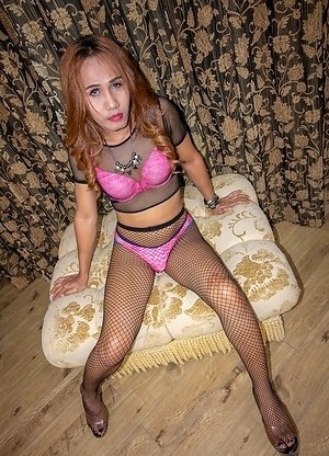 Ladyboy Yuki is wearing a pink bra and panties with a black mesh top and pantyhose.