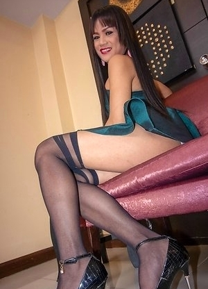 Ladyboy Khawn is wearing a little black dress with heels, stockings, and an appetite for cock in her mouth and asshole.