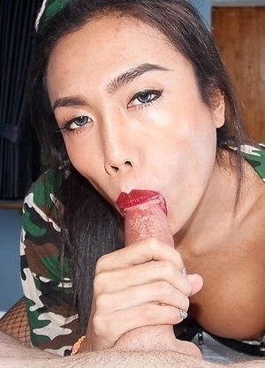 Busty Ladyboy Mos is wearing camo booty shorts and jacket. She strokes at the hard bulge under her shorts with legs spread.